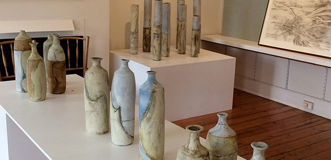 Foreground: Sarah Ormonde, Moving Earth, Safe Harbour series 2017, porcelain and terracotta mixed clay bottles. BACKGROUND: Sarah Ormonde, Rain Gauge series 2016, porcelain and terracotta mixed clay cylinders. John Wolseley, Found - Rainbow Country and Found - Sunset Tank, 2008, carbonised wood and natural stains on paper.